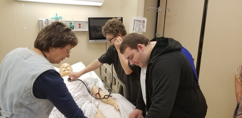 Students check vitals on a mannequin