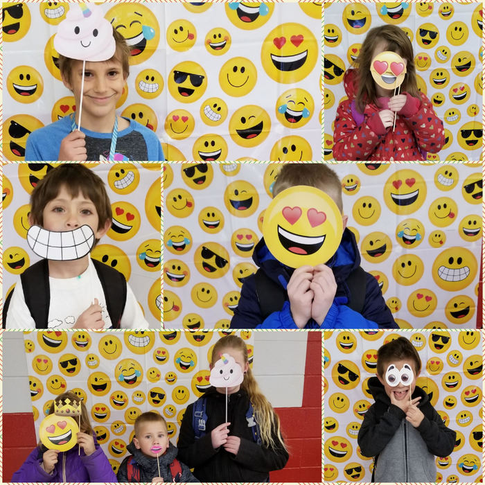 Students stand in front of an emoji background and hold props up